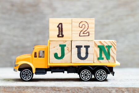 Truck hold letter block in word 12jun on wood background (Concept for date 12 month June)
