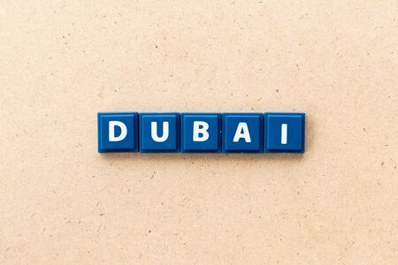 Tile letter in word Dubai on wood background