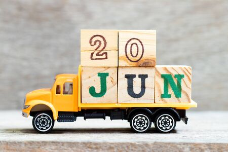 Truck hold letter block in word 20jun on wood background (Concept for date 20 month June)
