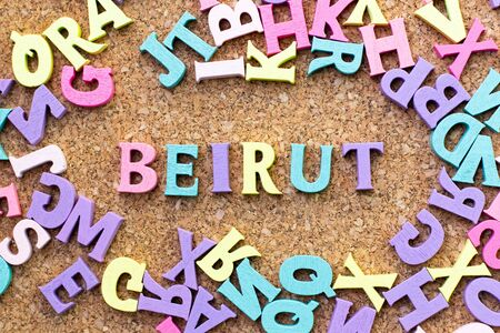Color alphabet in word Beirut with another letter as frame on cork board background