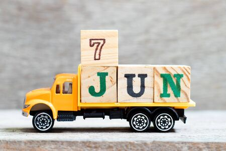 Truck hold letter block in word 7jun on wood background (Concept for date 7 month June)