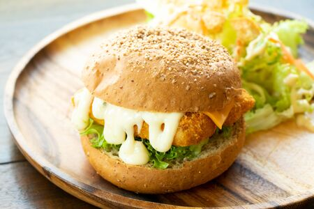 Fried fish fillet burger with vegetable salad on wood plate background