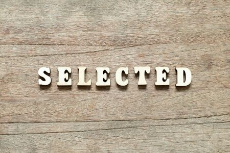Letter block in word selected on wood background
