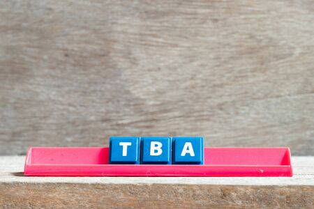 Tile letter on red rack in word TBA (abbreviation of to be announced) on wood background