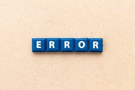 Tile letter in word error on wood background
