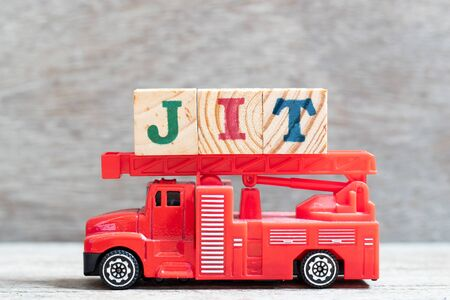 Red fire truck hold letter block in word JIT (abbreviation of just in time) on wood background