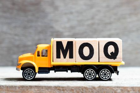 Truck hold letter block in word MOQ (Abbreviation of Minimum Order Quantity) on wood background Banco de Imagens