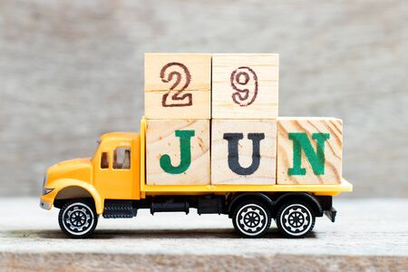 Truck hold letter block in word 29jun on wood background (Concept for date 29 month June)