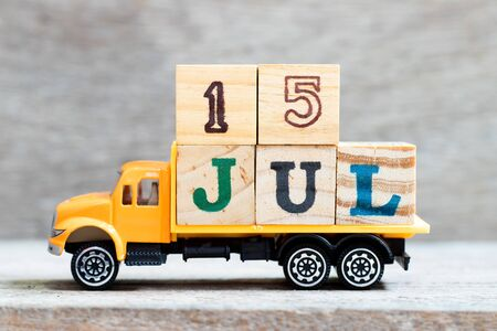 Truck hold letter block in word 15jul on wood background (Concept for date 15 month July)