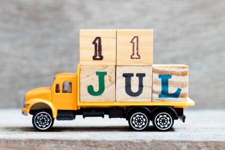 Truck hold letter block in word 11 jul on wood background (Concept for date 11 month July)