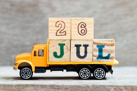 Truck hold letter block in word 26jul on wood background (Concept for date 26 month July)