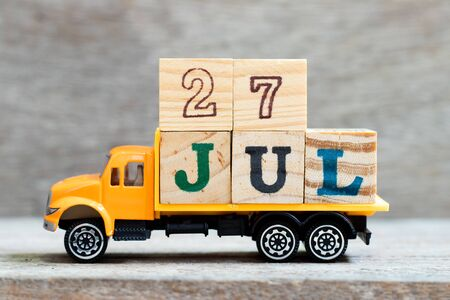 Truck hold letter block in word 27jul on wood background (Concept for date 27 month July) Banque d'images
