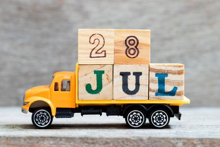 Truck hold letter block in word 28jul on wood background (Concept for date 28 month July) Banque d'images