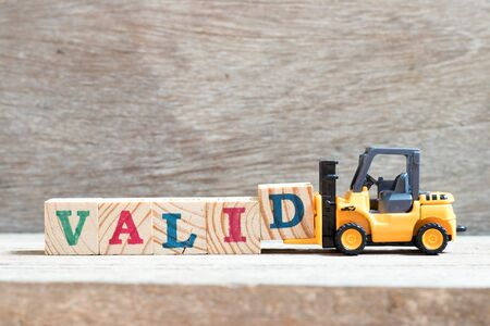 Toy forklift hold letter block d to complete word valid on wood background