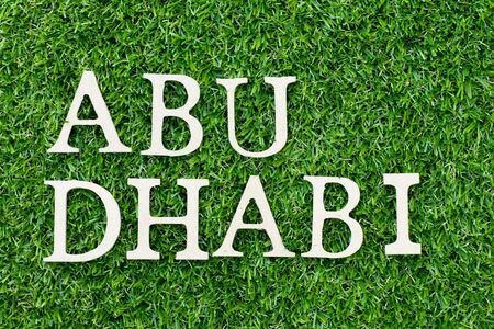 Wood alphabet letter in word Abu Dhabi on green grass background Stock fotó