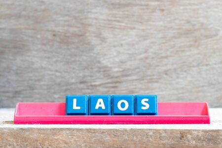 Tile letter on red rack in word laos on wood background Stock Photo