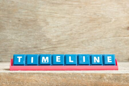 Tile letter on red rack in word timeline on wood background