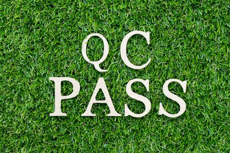 Wood alphabet letter in word QC (Abbreviation of Quality Control) pass on green grass background Stock Photo