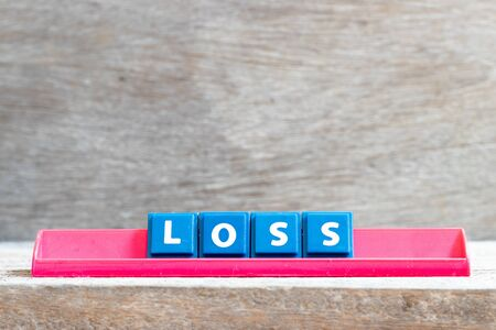 Tile letter on red rack in word lose on wood background