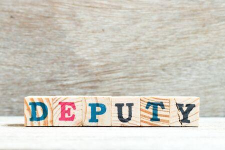 Letter block in word deputy on wood background
