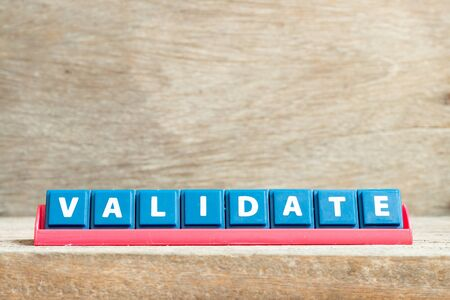 Tile letter on red rack in word validate on wood background