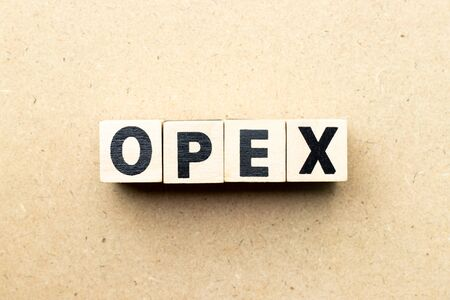 Letter block in word opex (abbreviation of operating expense) on wood background