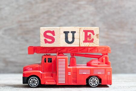 Red fire truck hold letter block in word sue on wood background