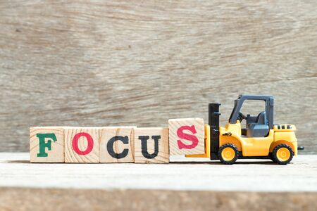 Toy forklift hold letter block s to complete word focus on wood background