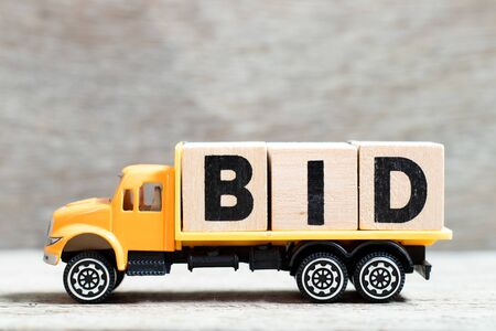 Truck hold letter block in word bid on wood background Banque d'images