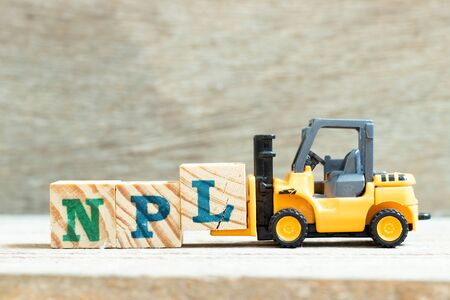 Toy forklift hold letter block l to complete word NPL (Abbbreviation of Non Performing Loan, Non-Patent Literature) on wood background