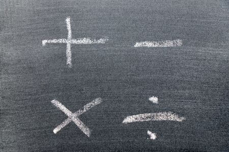 White color chalk hand drawing in mathematics symbol shape (Plus, minus, multiply, divide) on black board background