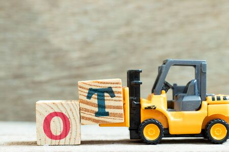Toy forklift hold letter block T to complete word ot (abbreviation for overtime) on wood background Foto de archivo