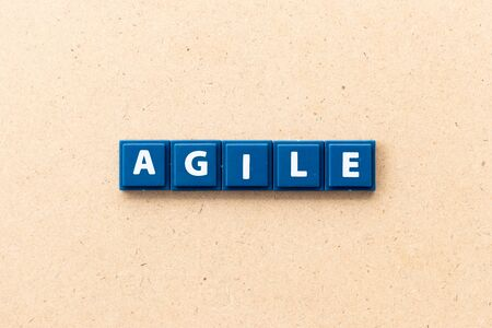 Tile letter in word agile on wood background