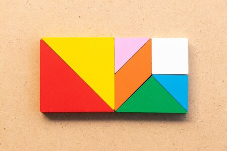 Color tangram puzzle in square shape on wood bacground