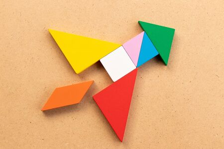 Color tangram puzzle in rocket or missile shape on wood bacground (Concept for new experience, start up the business)