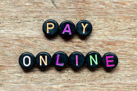 Black bead with color letter in word pay online on wood background