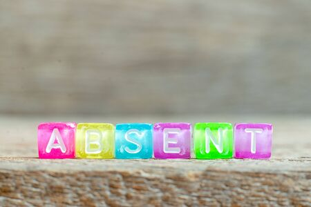 Clear bead with white letter in word absent on wood background Stockfoto
