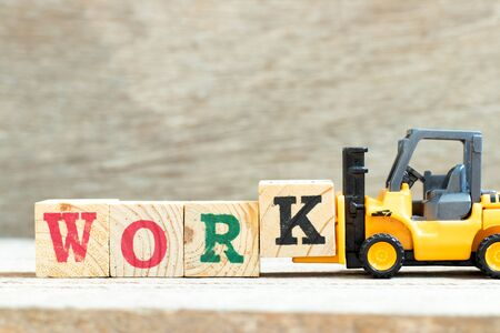 Toy forklift hold letter block k to complete word work on wood background