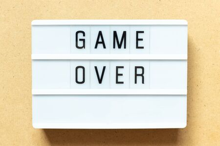 Lightbox with word game over on wood background