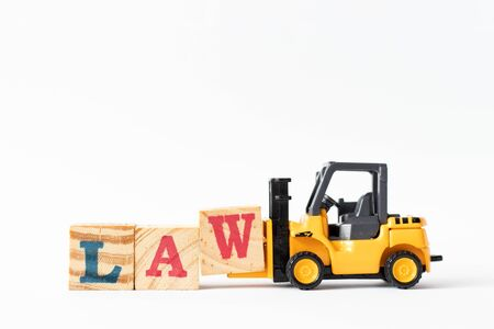 Toy forklift hold wood letter block W to complete word law on white background Stock Photo