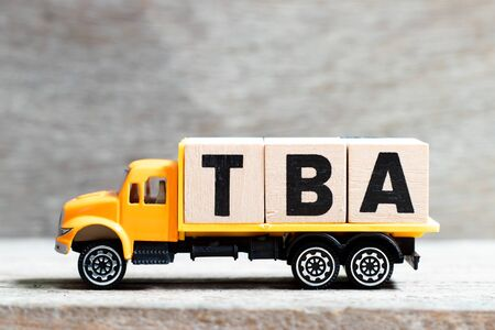 Truck hold letter block in word TBA (abbreviation of to be announced) on wood background