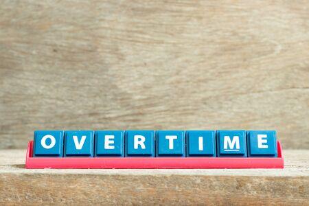 Tile letter on red rack in word overtime on wood background Foto de archivo