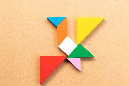 Color tangram puzzle in flying bird shape on wood bacground