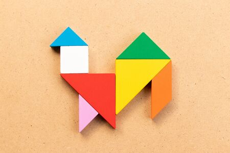 Color tangram puzzle in cock or bird shape on wood bacground Imagens