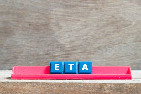 Tile letter on red rack in word ETA (abbreviation of estimated time of arrival) on wood background