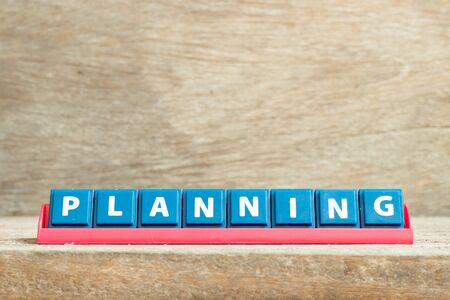 Tile letter on red rack in word planning on wood background