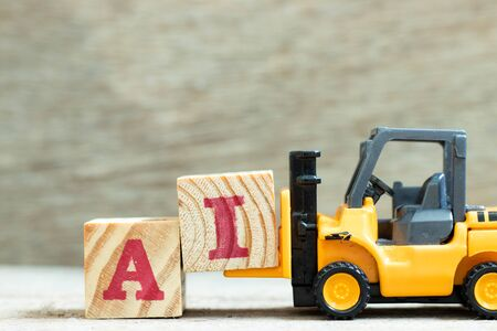 Toy forklift hold letter block I to complete word AI (Abbreviation of artificial intelligence) on wood background