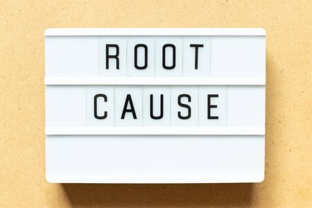 Lightbox with word root cause on wood background
