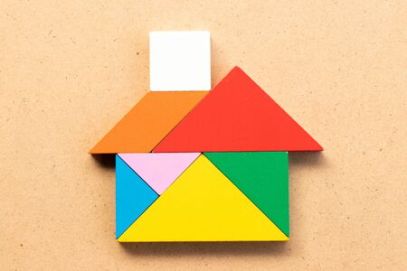 Color tangram puzzle in home shape on wood bacground 写真素材