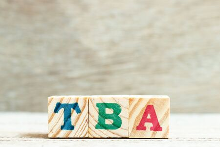 Alphabet letter in word TBA (abbreviation of to be announced) on wood background